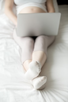Woman lying in bed with a laptop on legs
