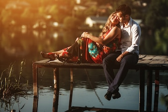 Woman lying on her husband on a bridge