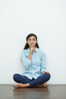 Woman Making Silence Gesture and Sitting on Floor