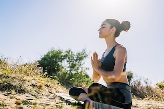 Woman meditating on a sunny day at the beach
