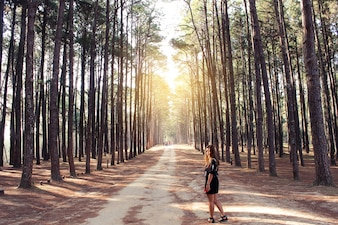 Woman on a dirt road with trees at the sides