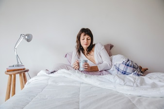 Woman on bed looking at her coffee