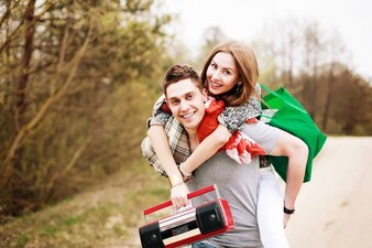 Woman on the back of her boyfriend and holding a boombox