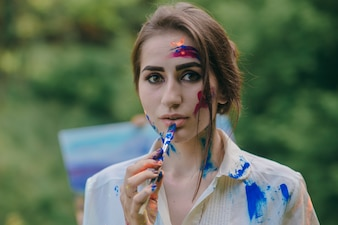 Woman painting a blue lip with a paintbrush