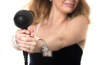 Woman pointing at herself with a hairdryer