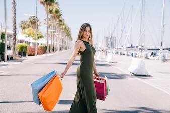 女性、ポーズをとって、ショッピングバッグで遊ぶ