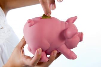 Woman puttingcoin into a piggybank