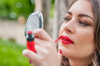 女性が置く、赤い口紅リップグロスを修正する。コーヒーショップレストラン街の屋外の背景。ミックスレースモデル