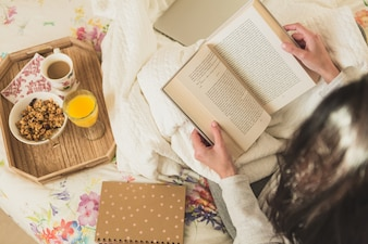 Woman reading a book while having breakfast