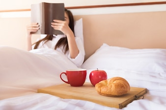 Woman reading book  and drinking coffee on bed during the morning
