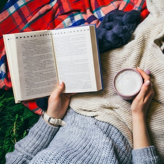 Woman reads book holding cup of coffee and lying under colorful plaids