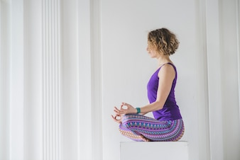 Woman relaxing and meditating at home