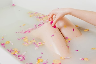 Woman relaxing in bath with flowers