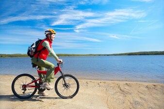 Woman riding a bike next to the lake