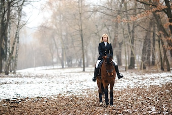Woman riding horse in woods