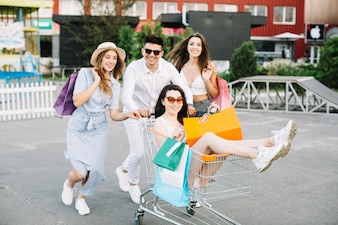 Woman riding shopping cart with her friends
