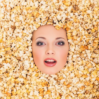 Woman's face popping out of popcorn