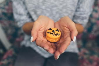 Woman's hands with a pumpkin cookie