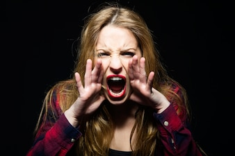 Woman screaming with hands on face