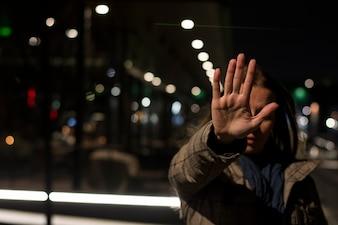 夜、立っている間、手を止めているサインを示す女性