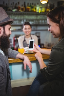 Woman showing mobile phone to man