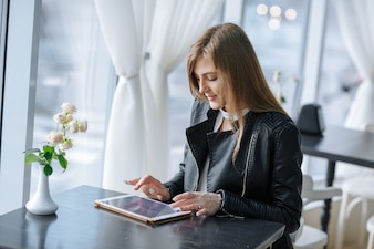 Woman sitting at a restaurant touching a tablet