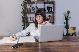 Woman sitting at table with laptop and taking notes