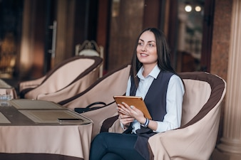 Woman sitting in an elegant restaurant with a tablet
