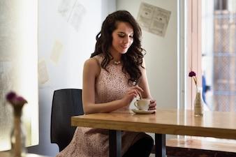女性は、都市のカフェに座ってコーヒー杯に小さじを移動します。