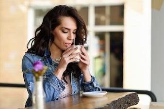 カジュアルな服を着ている都市カフェで屋内に座っている女性