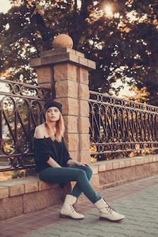 Женщина сидит на перила с меланхолическим взглядом