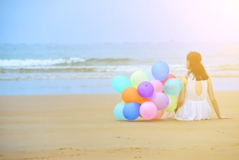 Woman sitting on the sand next to a bunch of balloons