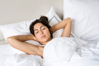 Woman sleeping with her hands on her head