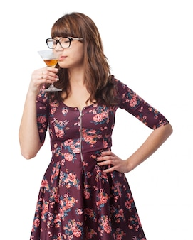 Woman smelling a glass with alcohol with eyes closed
