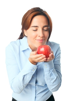 Woman smelling a red apple