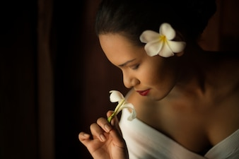 Woman smelling a white flower close