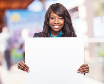 Woman smiling holding a white poster