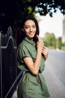Woman smiling next to a fence with a green dress