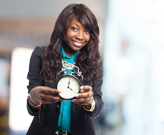 Woman smiling while holding an alarm clock