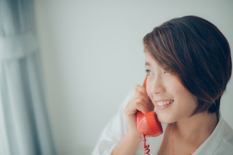Woman smiling while talking on a red phone close up