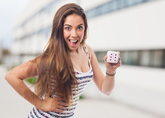 Woman smiling with a dice with the face of the six