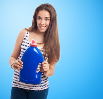 Woman smiling with a pot of blue detergent
