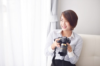Woman smiling with a reflex camera