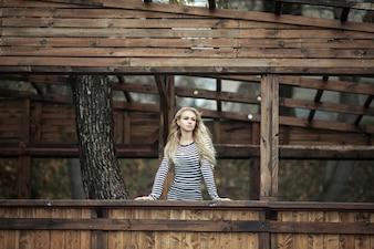 Женщина, стоящая в деревянном уличном доме