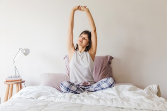 Woman stretching arms on bed in the morning