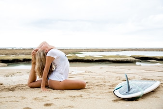 Woman Stretching Body by Surfboard on Beach