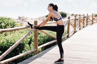 Woman stretching leg at beach