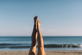 Woman stretching legs lying at the beach