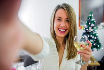 Woman take selfie on phone with Christmas tree hold glass of vine, celebrating New Year. christmas concept - young woman taking selfie photo near decorated christmas tree