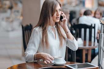 Woman talking on the phone and holding a cup of coffee